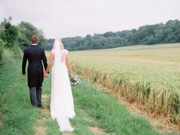 Bride and groom in wheat field captured by luxury film wedding photographer Camilla Arnhold