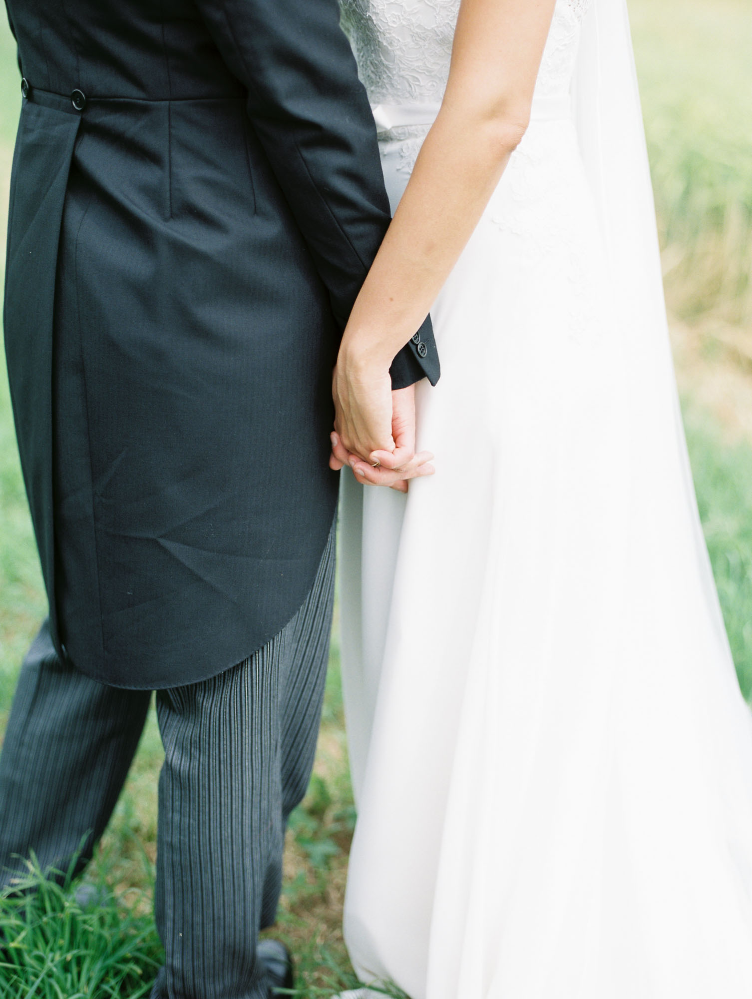 Close up photograph of bride and groom holding hands