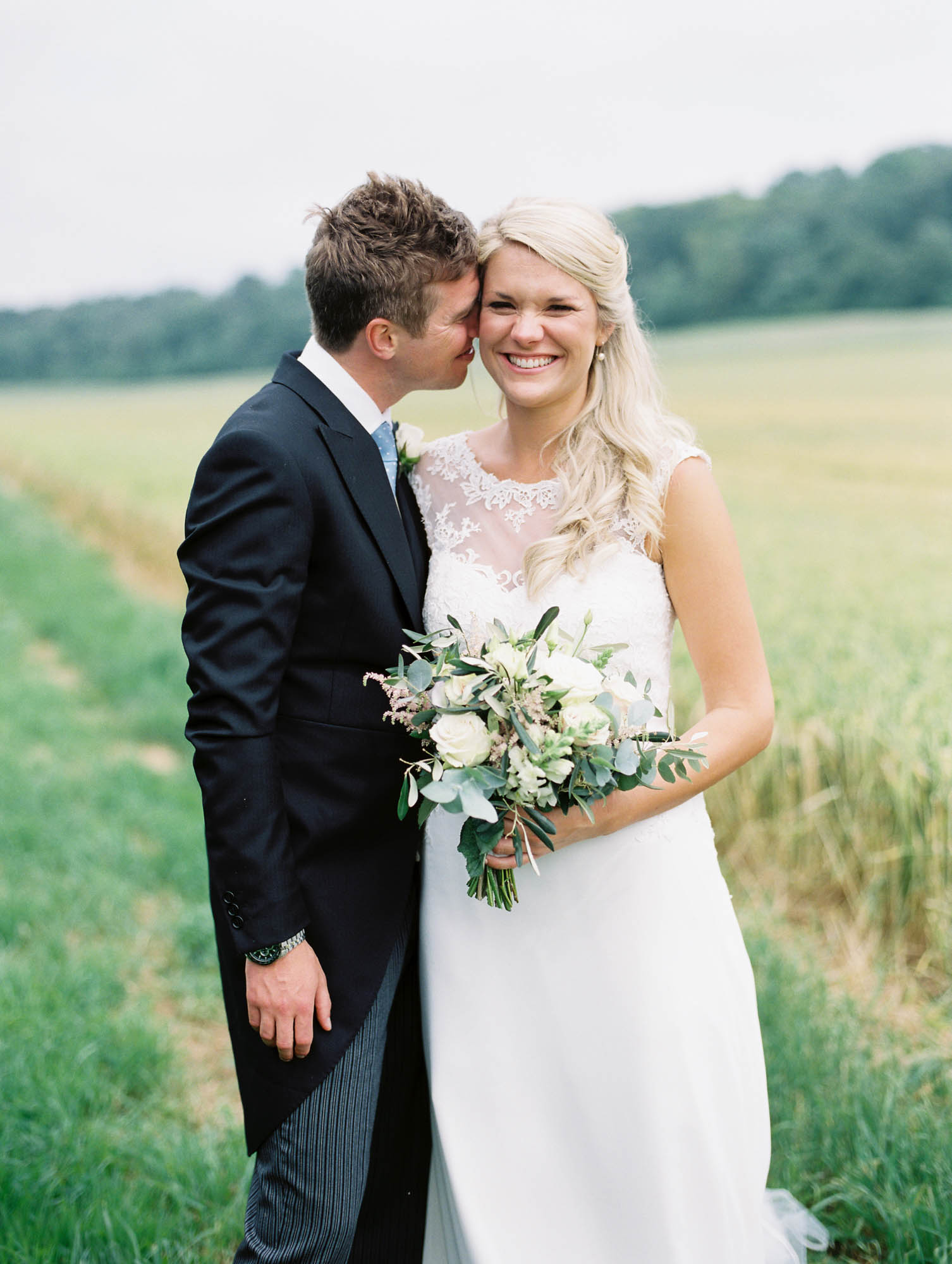 Natural laughter of bride and groom in wheat field captured by luxury film wedding photographer Camilla Arnhold
