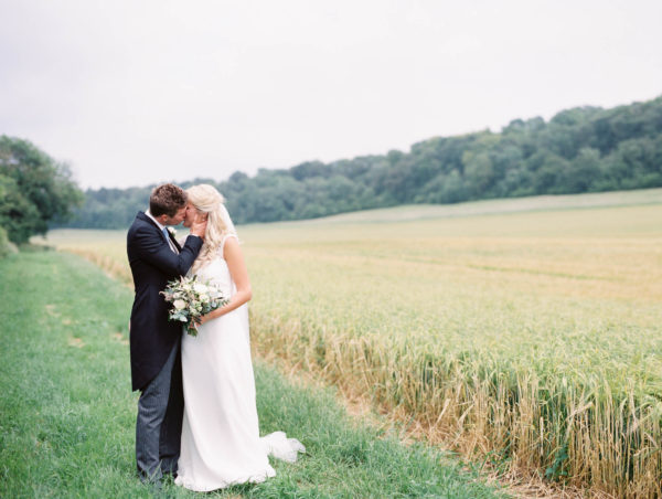 Bride and groom kissing in wheat field captured by luxury film wedding photographer Camilla Arnhold