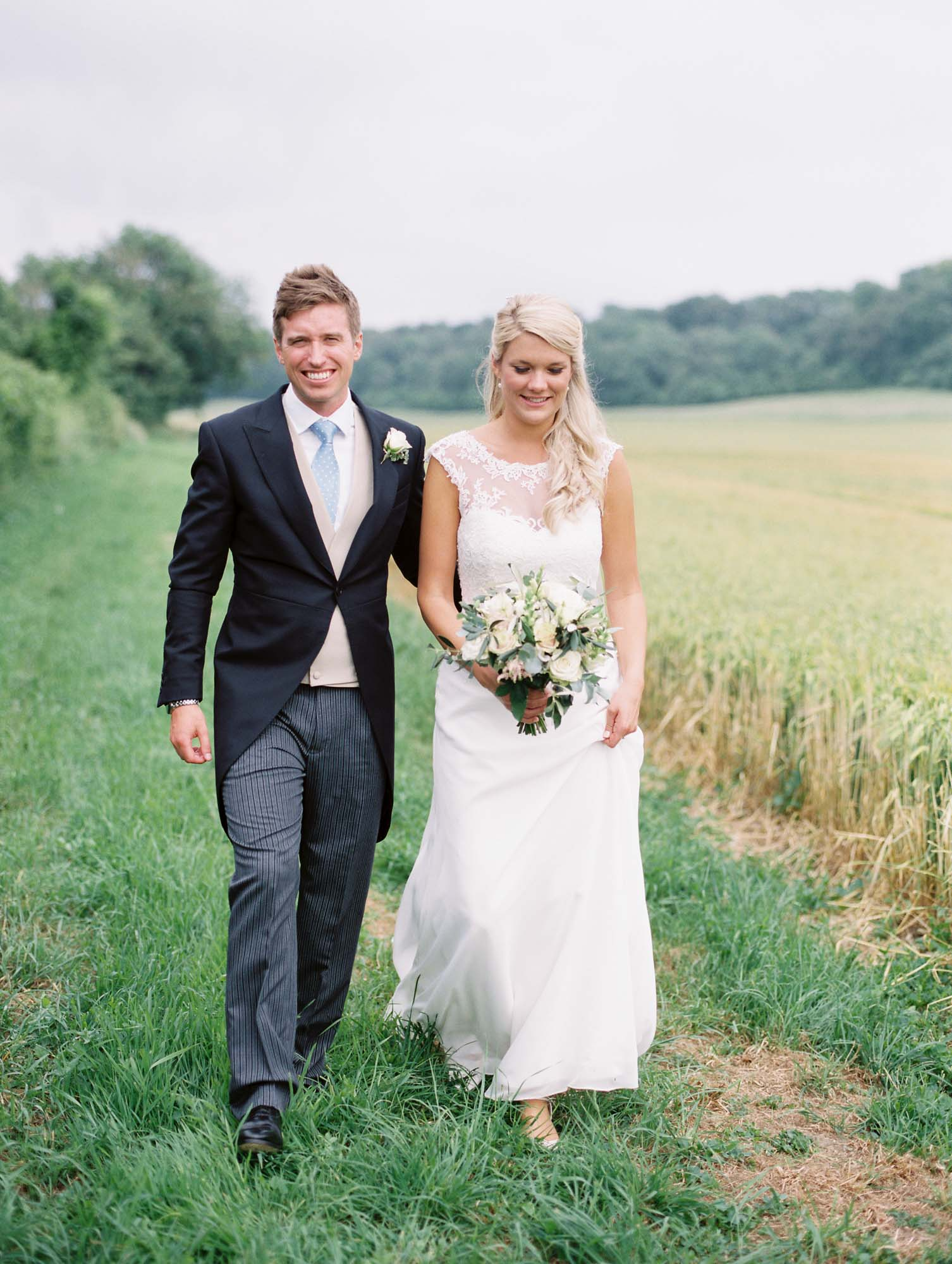 Bride and groom walking next to wheat field captured by luxury film wedding photographer Camilla Arnhold