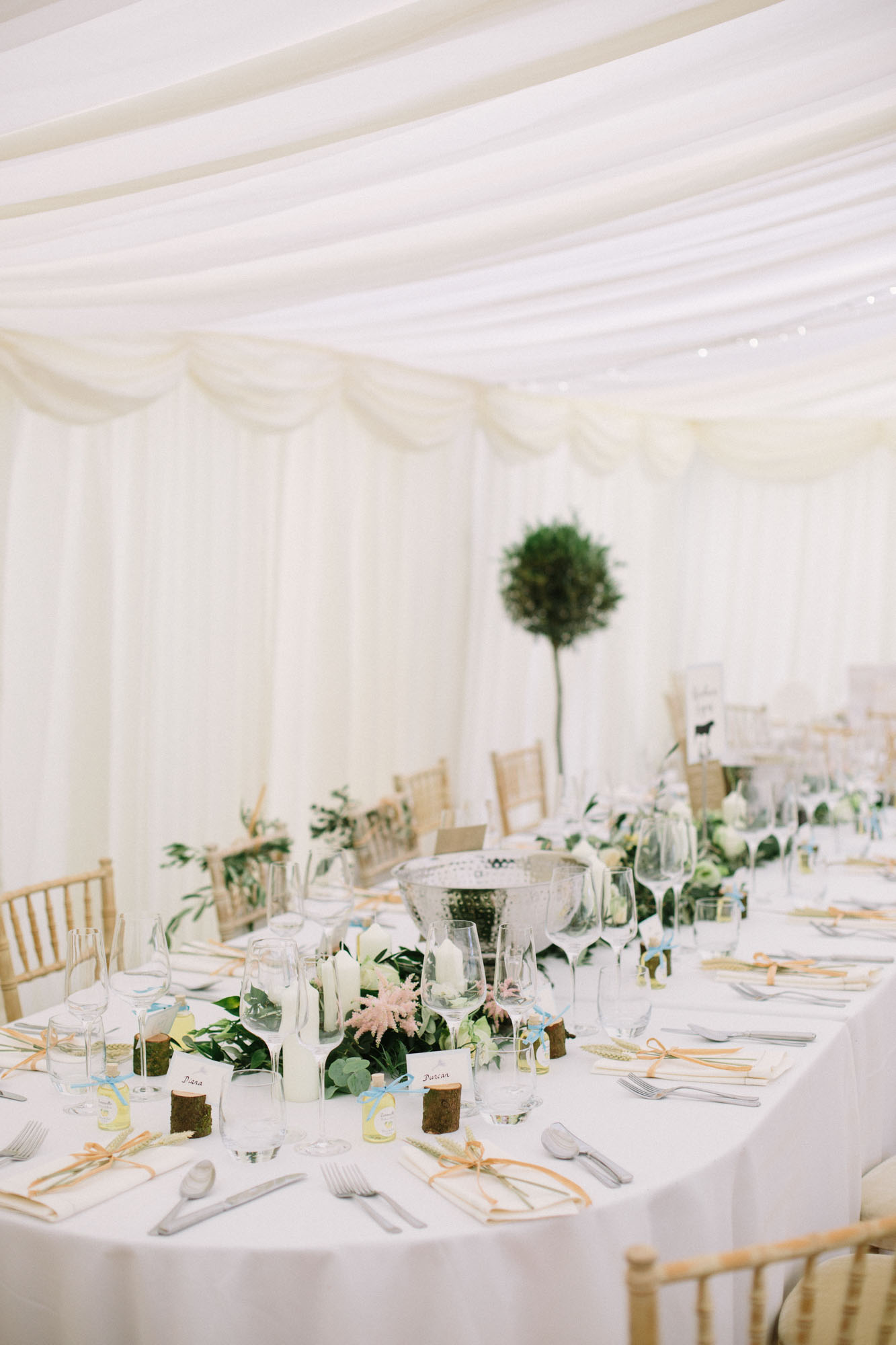 Top table decorated with white, green and pink flowers in marquee at Sussex Garden Wedding