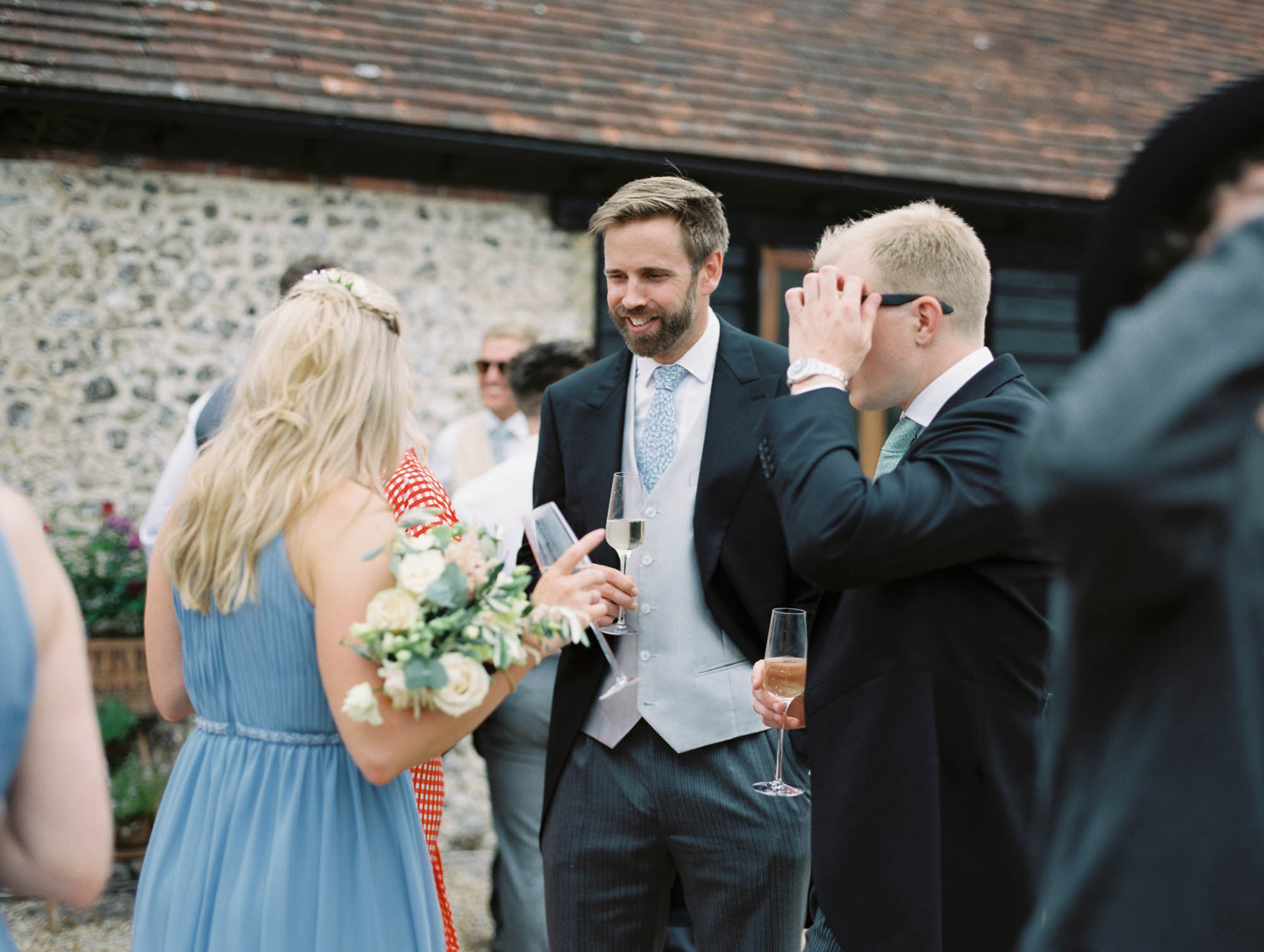 Sophisticated wedding guests mingling outside at Sussex Garden Wedding