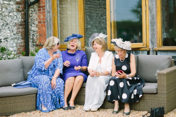 Wedding guests sitting on a sofa and laughing