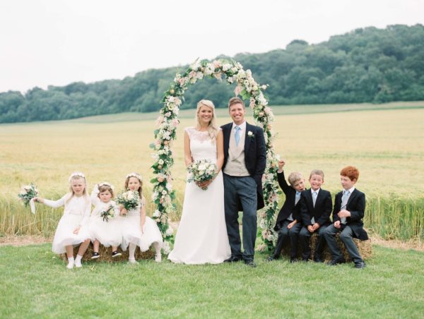 Bride and groom with flower girls and page boys under flower arch in front of a wheat field