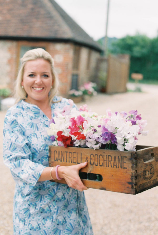 Bridesmaid carrying box of sweet peas