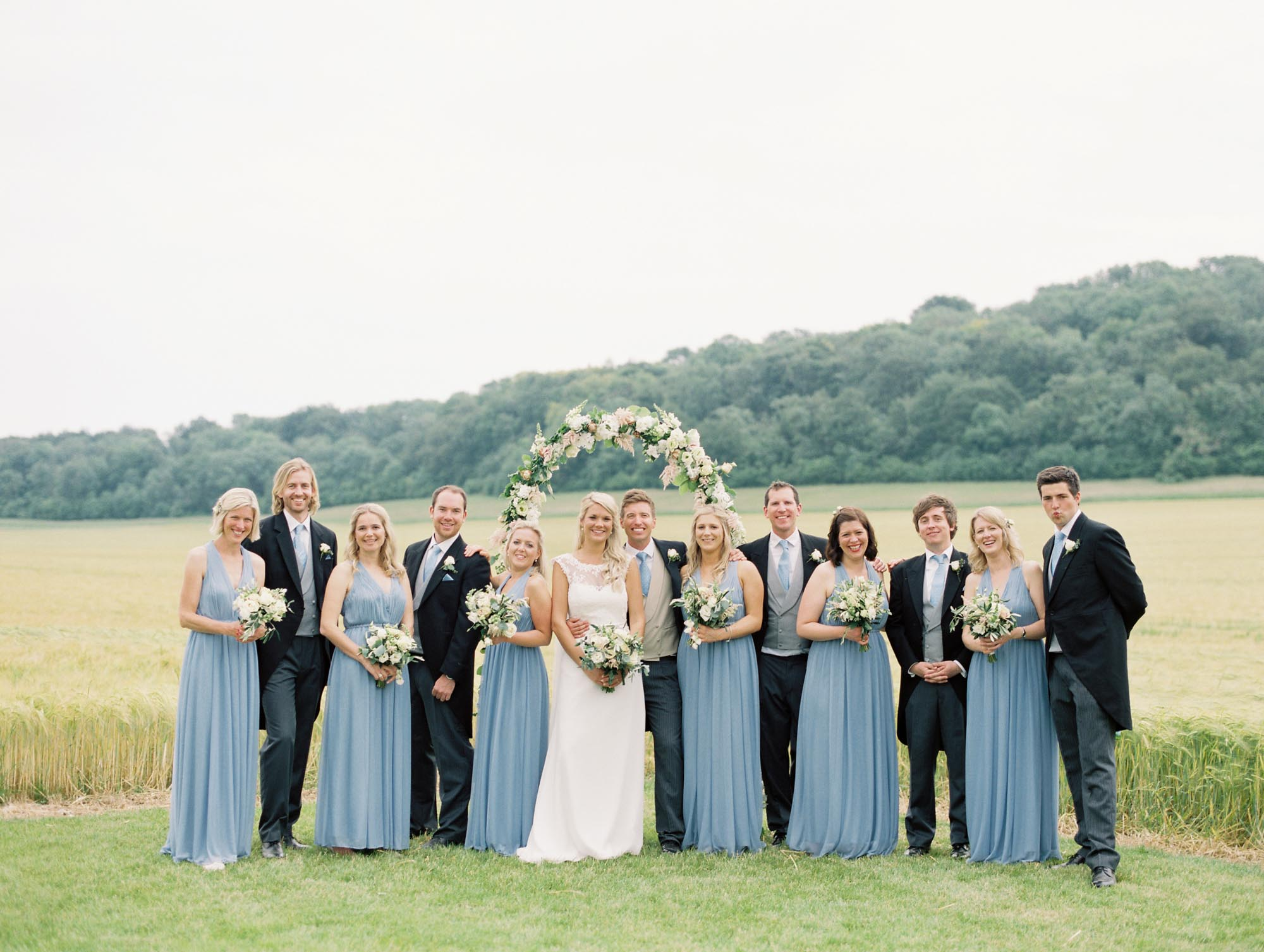 Wedding party in natural group photo captured by luxury film wedding photographer Camilla Arnhold