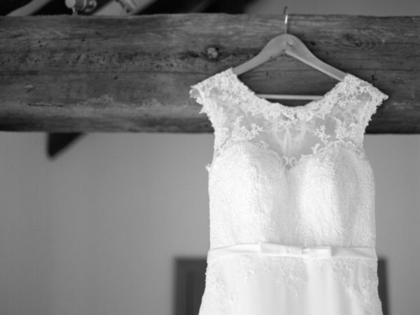 Black and white photograph of wedding dress hanging on wooden beam