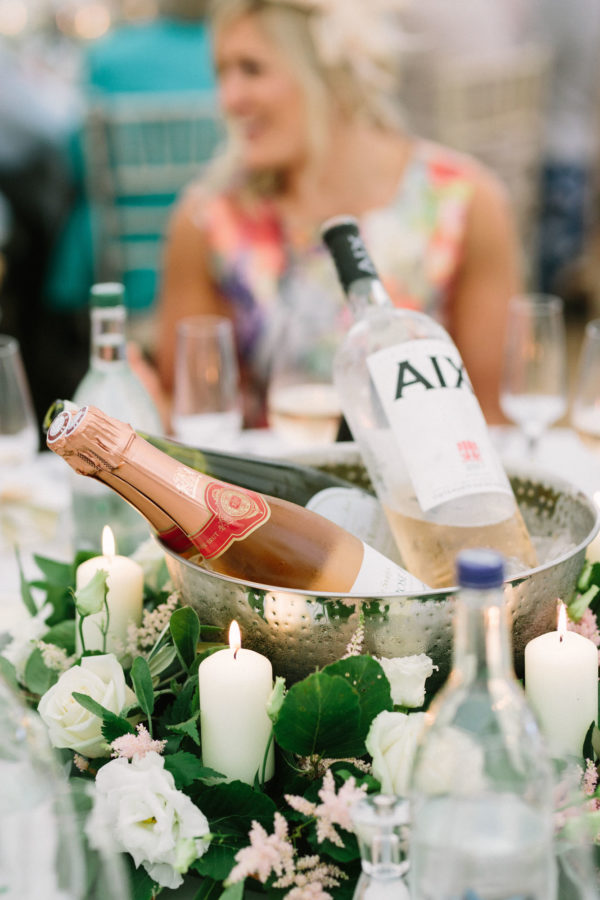 Silver bowls filled with wine and champagne bottles in marquee at Sussex Garden Wedding