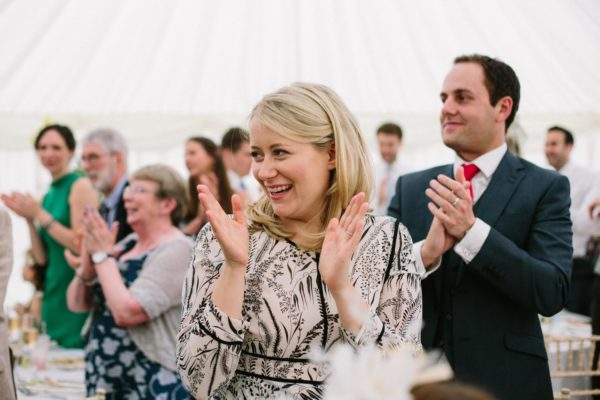 Wedding guests applauding entrance of bride and groom into marquee