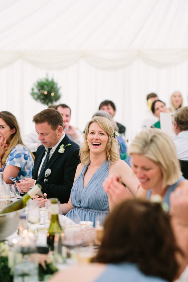 Bridesmaid laughing during wedding speeches