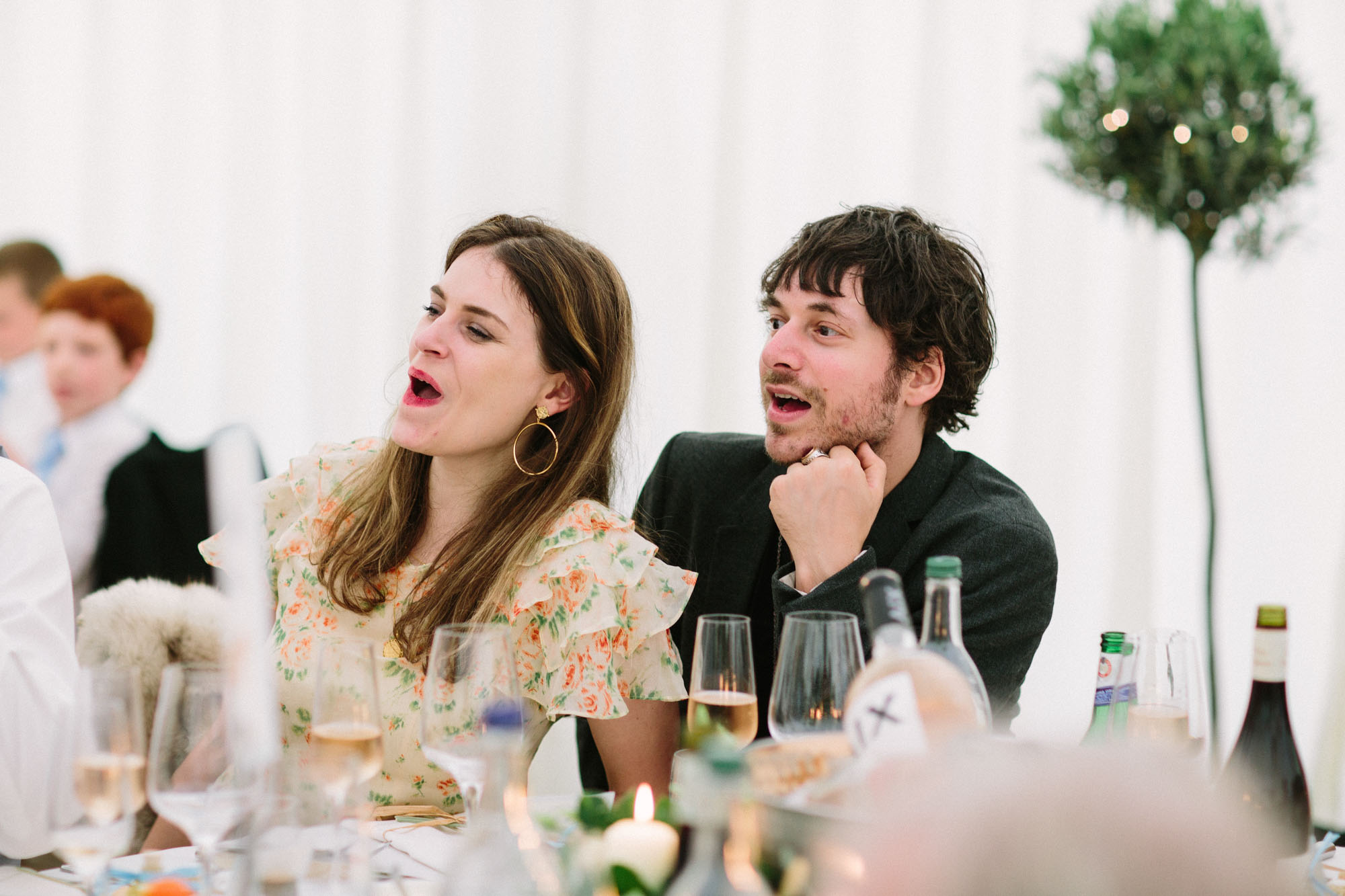 Wedding guests cheering and laughing during speeches in marquee