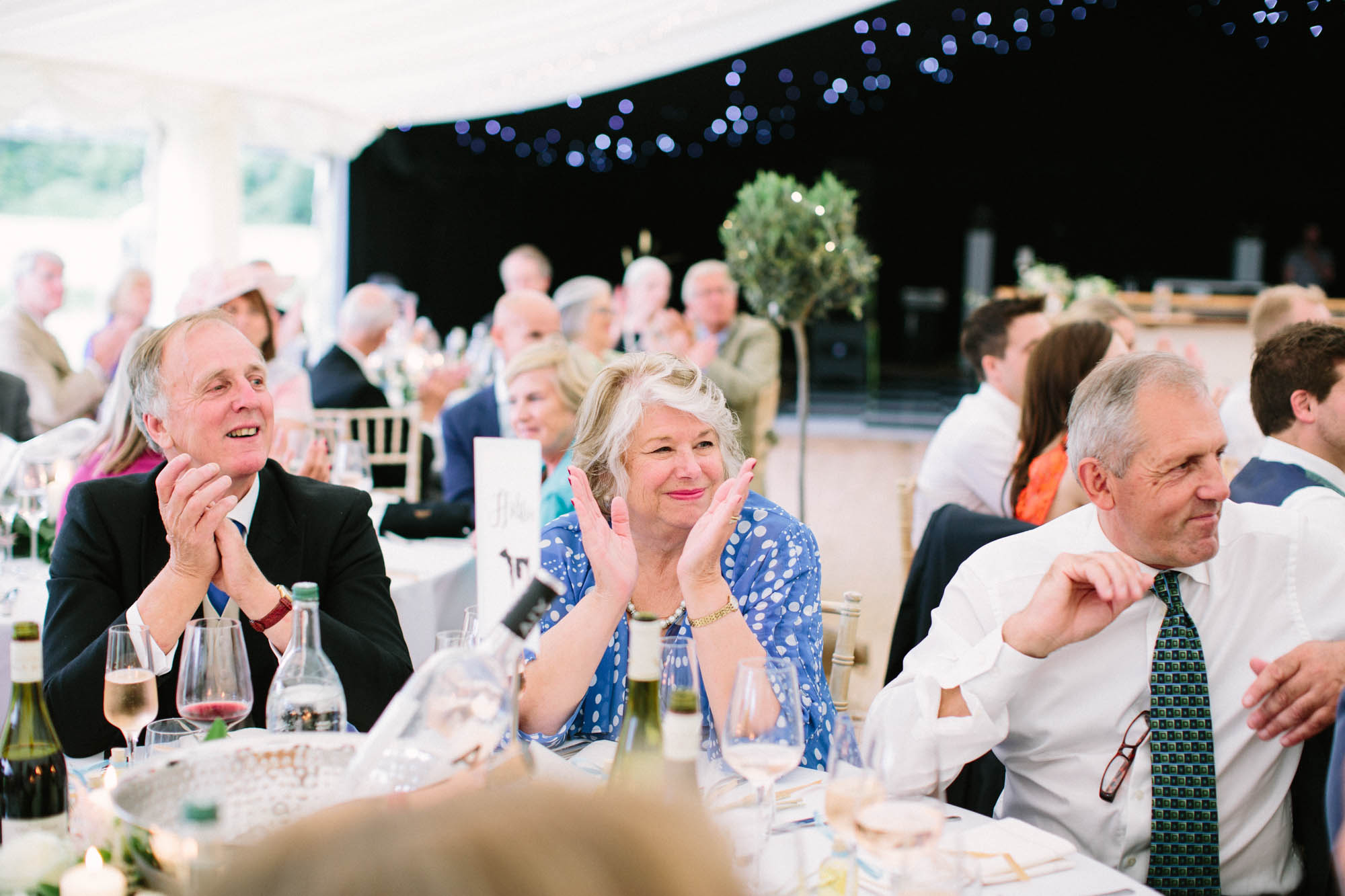 Wedding guests laughing and clapping during wedding speeches at Sussex Garden Wedding