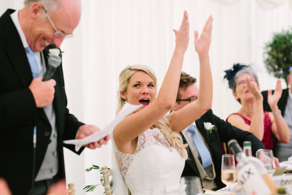 Bride cheering her father during his wedding speech