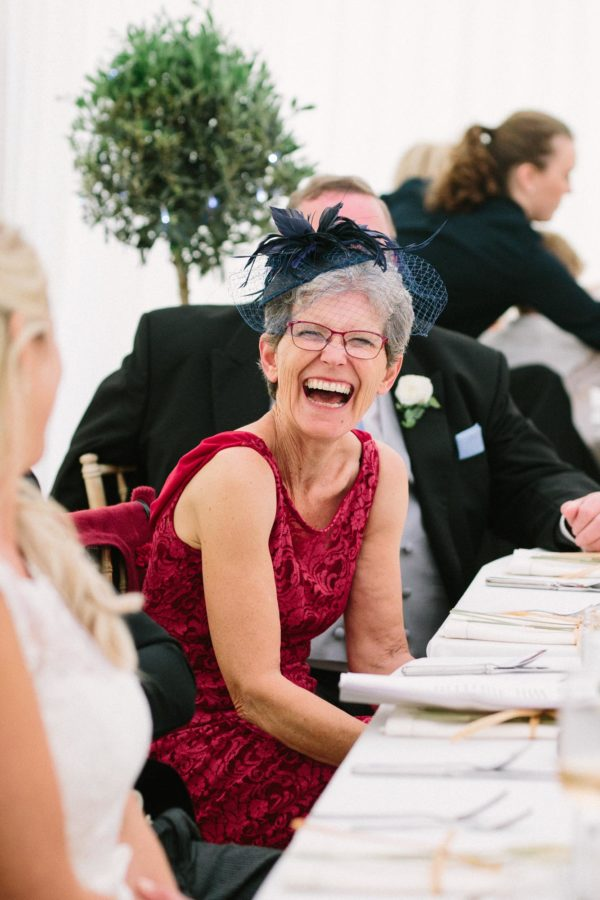 Mother of the groom laughing during father of bride speech