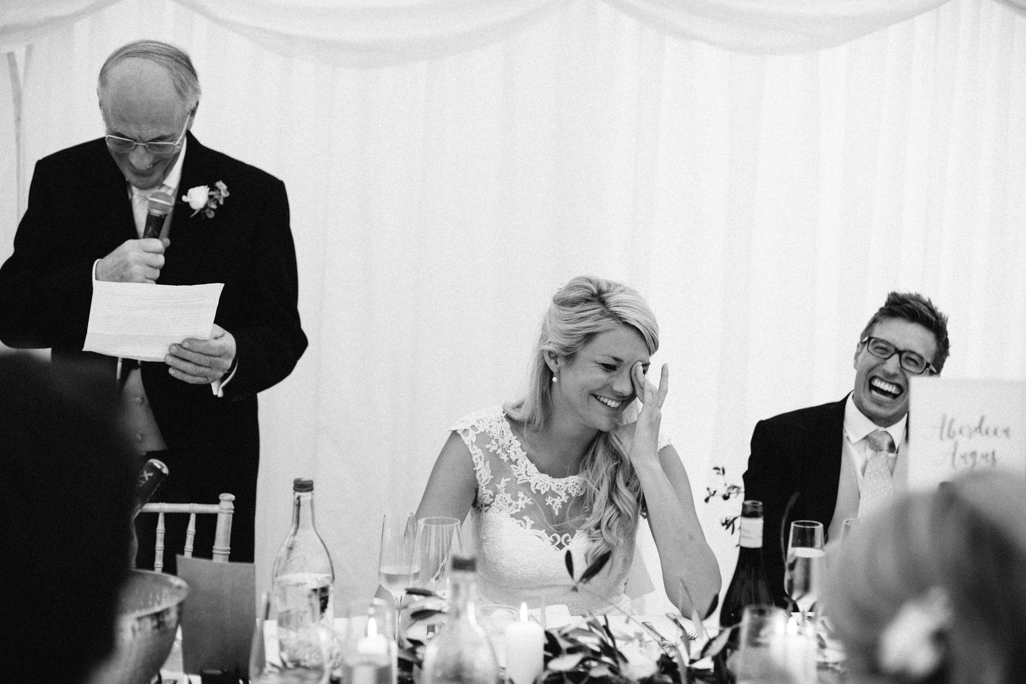 Bride laughing and crying during her father's wedding speech