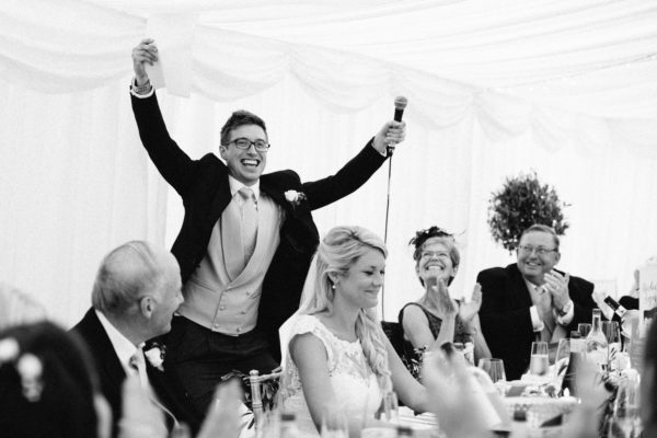 Groom raising his arms to applause during his wedding speech