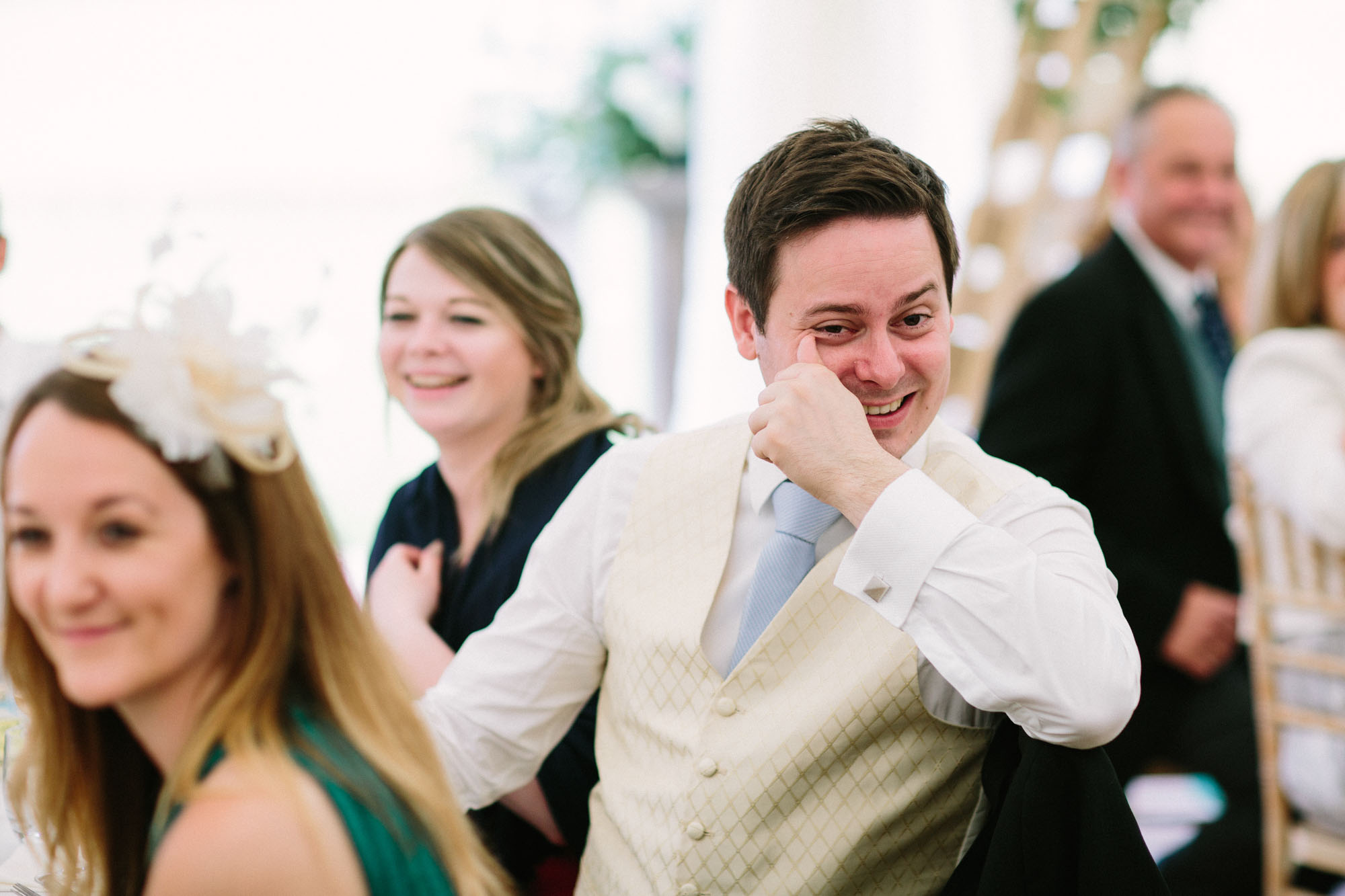 Male wedding guest crying with laughter during grooms speech