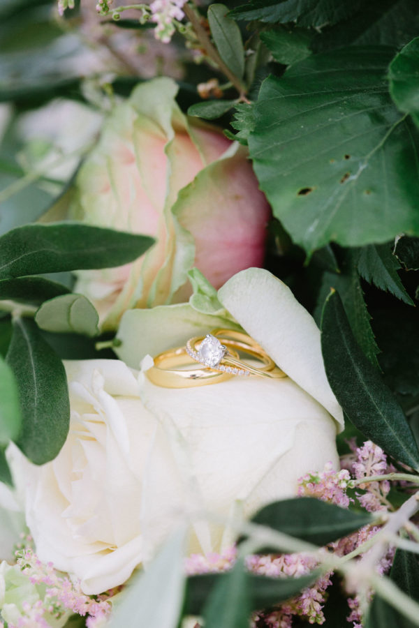 Close up photograph of wedding rings and engagement ring amongst cream, green and pink flowers