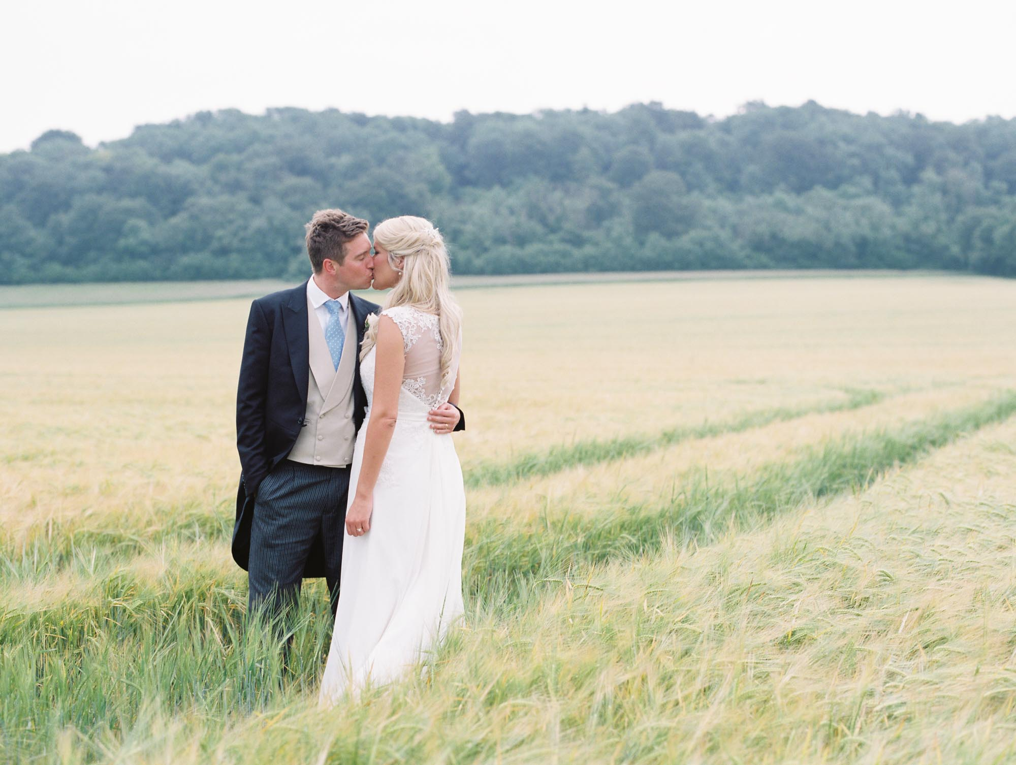 Bride and groom kissing in wheat field at Sussex Garden Wedding
