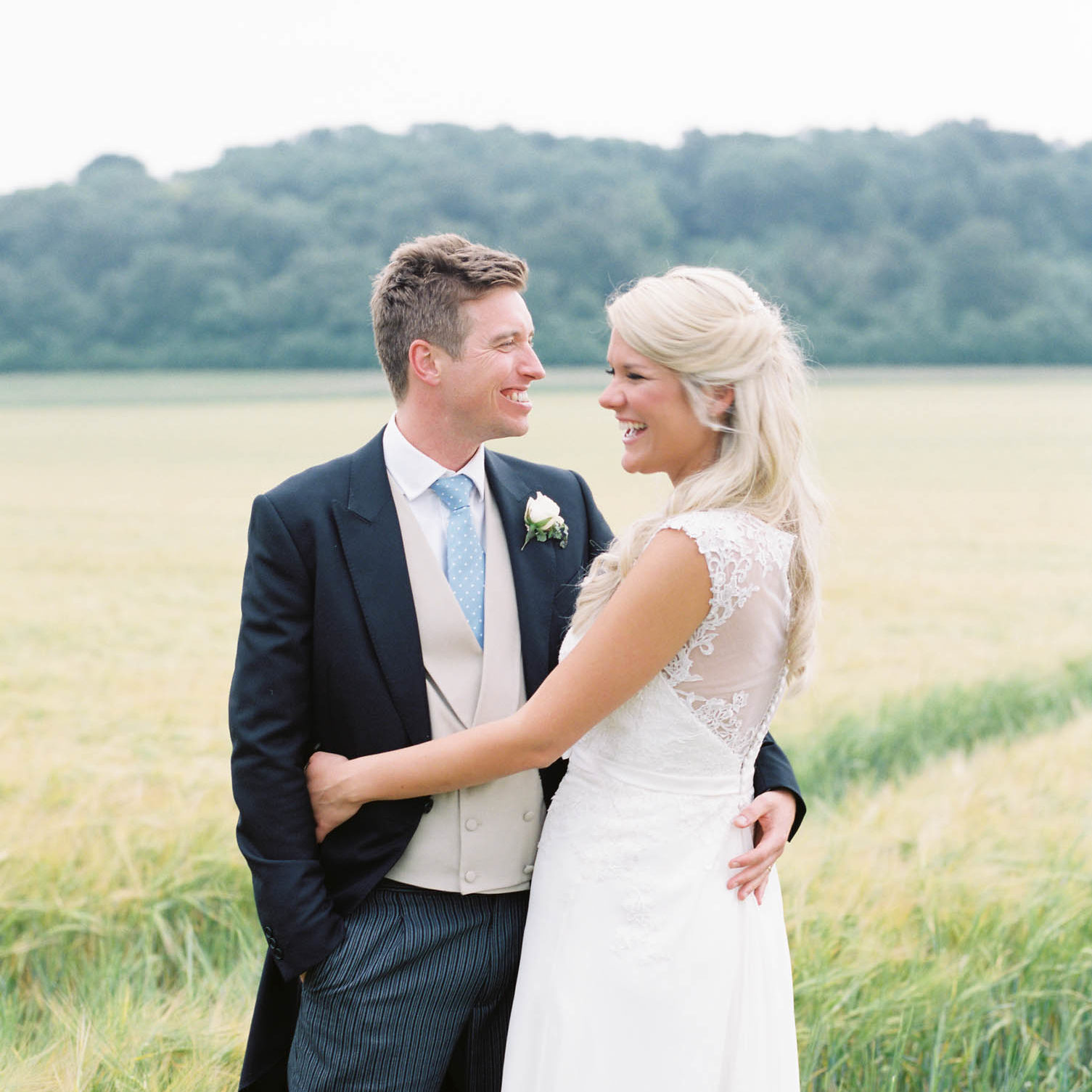Bride and groom hugging and laughing in wheat field