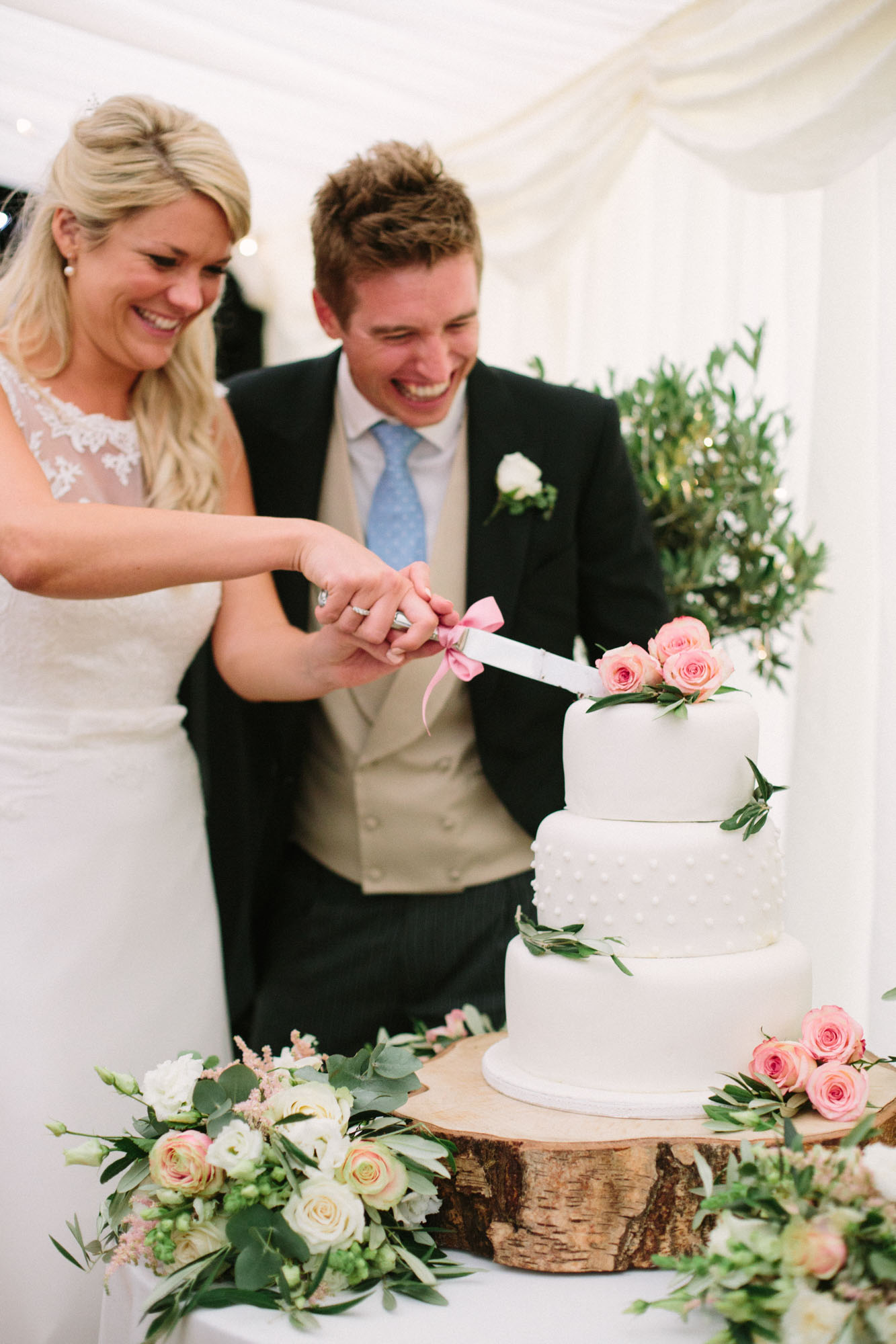 Bride and groom cutting three tiered white wedding cake decorated with pink roses