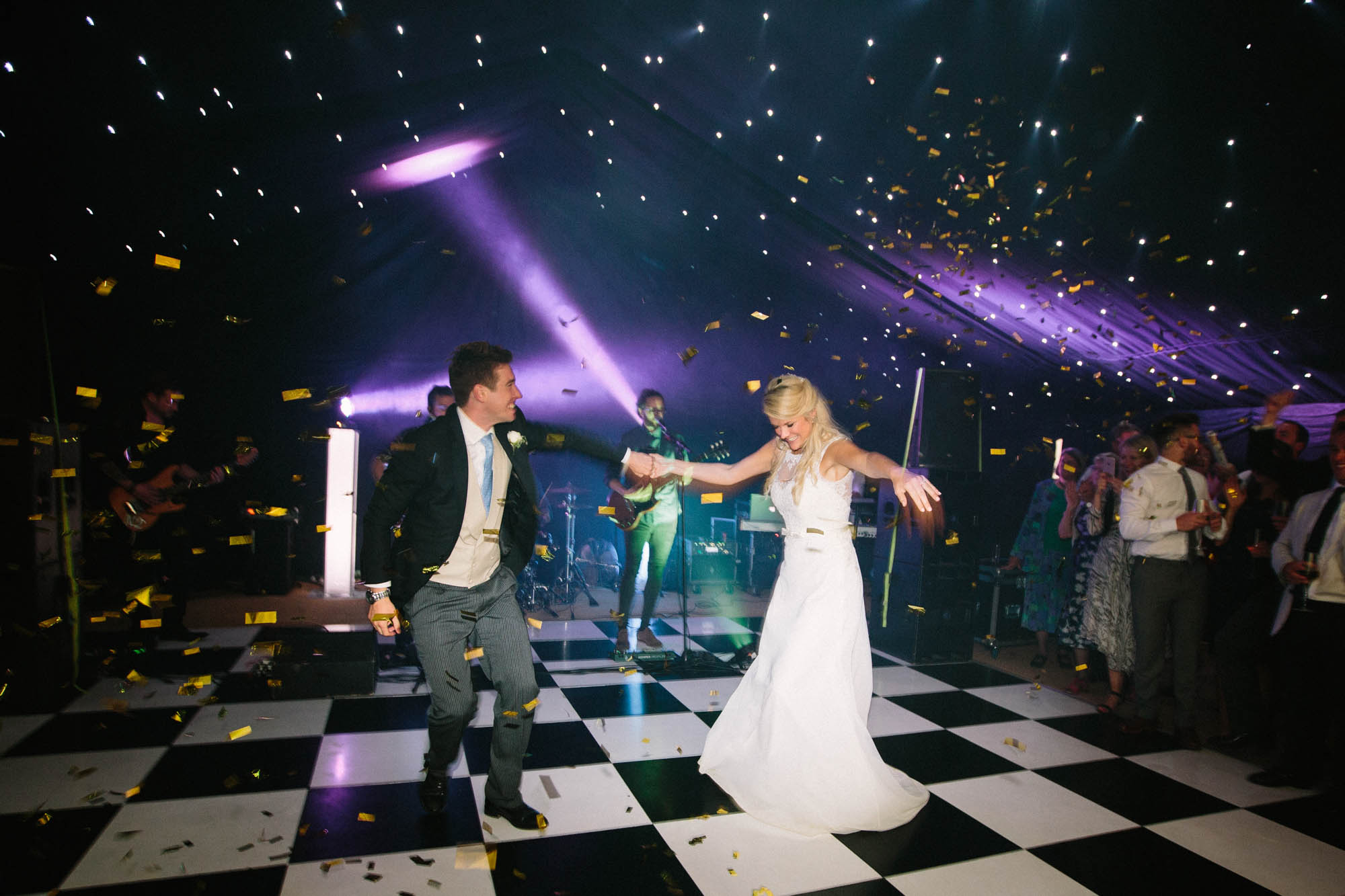 Bride and groom performing first dance with gold confetti showering down on them