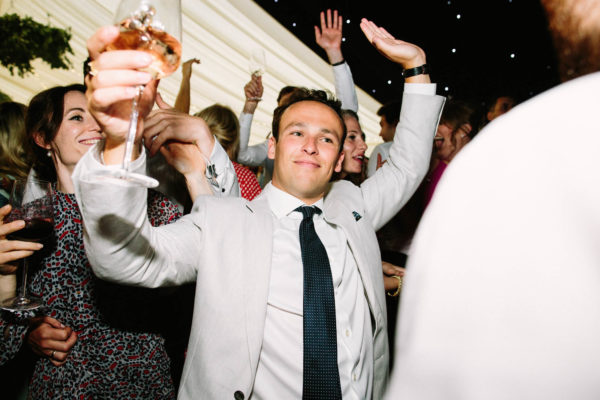 Wedding guests dancing and drinking pink champagne