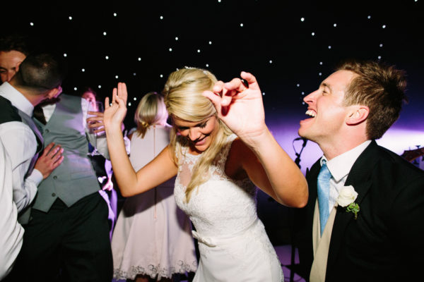Bride and groom laughing and dancing at Sussex Garden Wedding