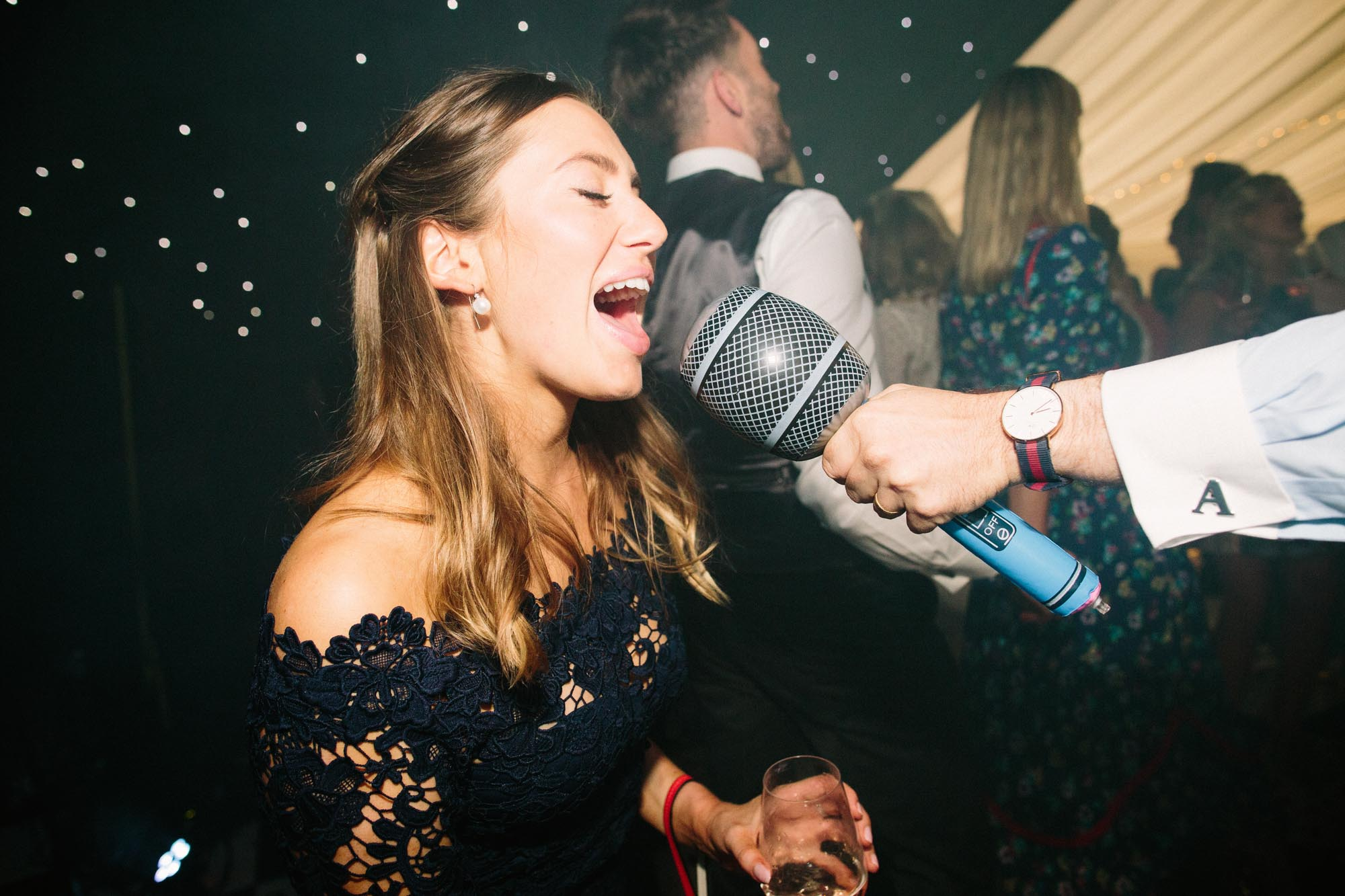 Wedding guest singing into inflatable microphone
