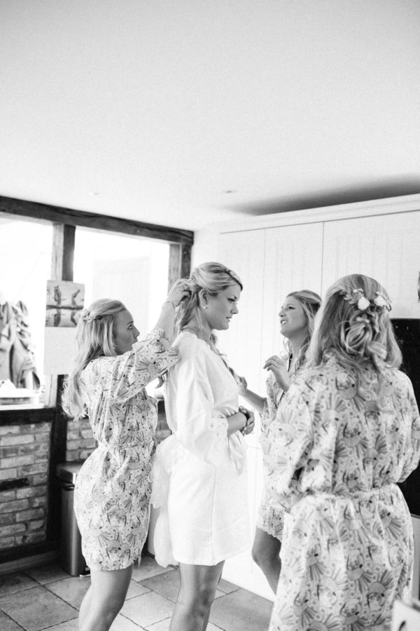 Bride having hair adjusted by bridesmaids all wearing matching dressing gowns