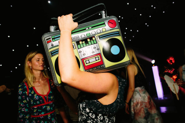 Wedding guest carrying inflatable boom box on dance floor