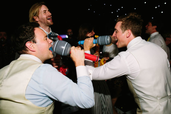 Groom and ushers singing into inflatable microphones on the dance floor at Sussex Garden Wedding