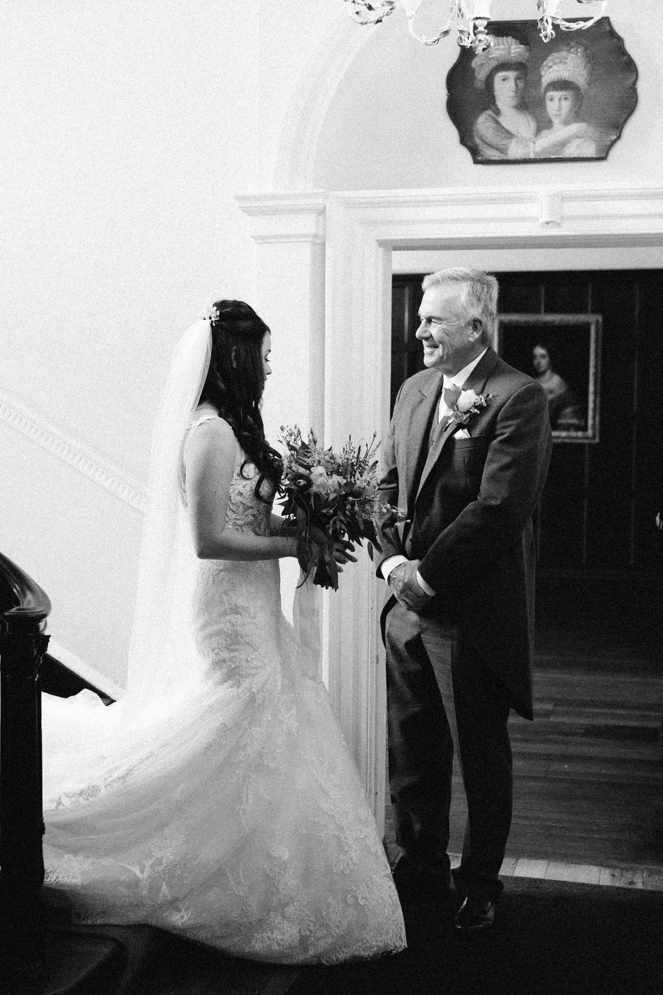 Father of the bride greeting bride at the bottom of a staircase