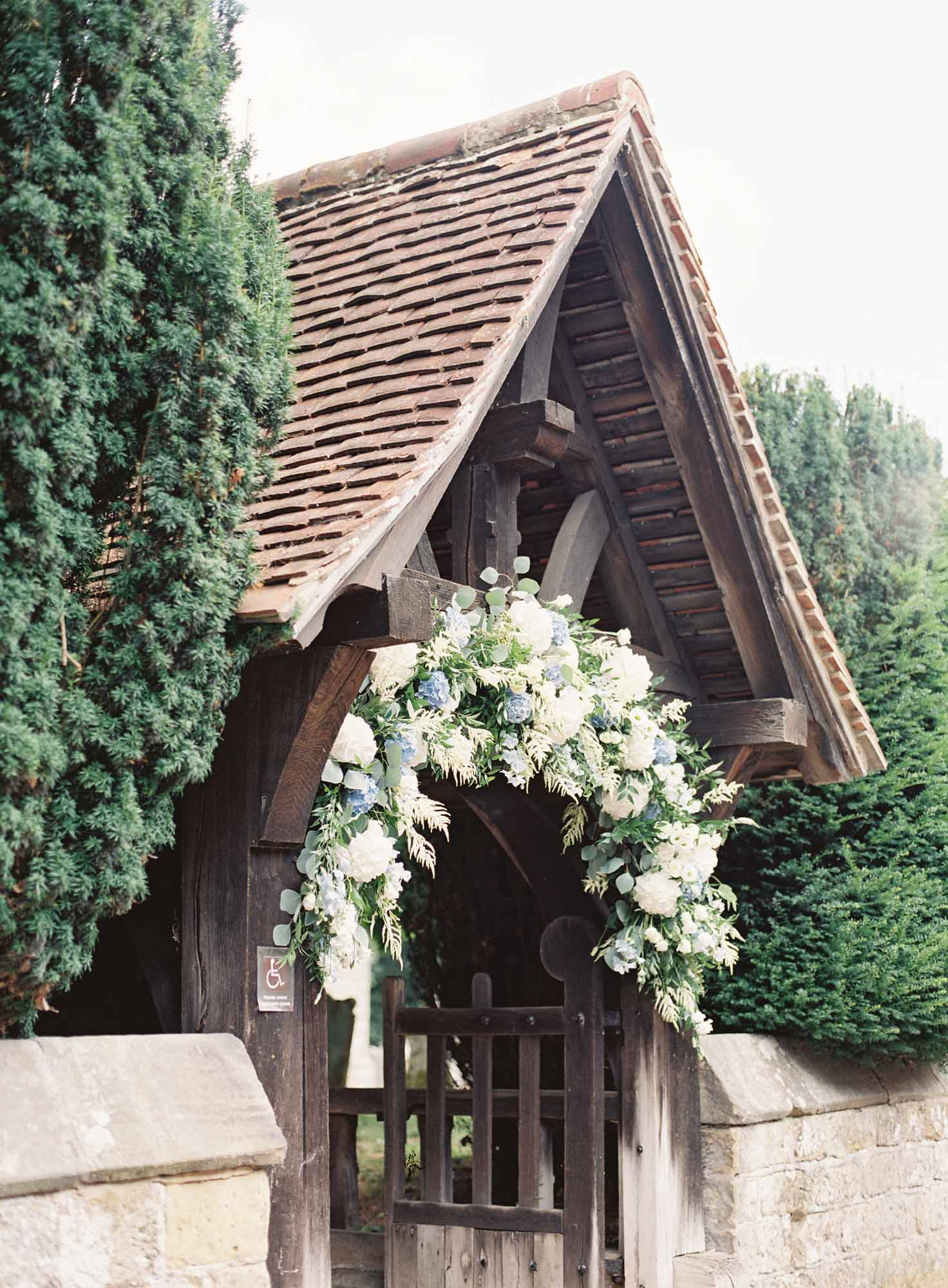Flower arch in blue, white and green at church wedding