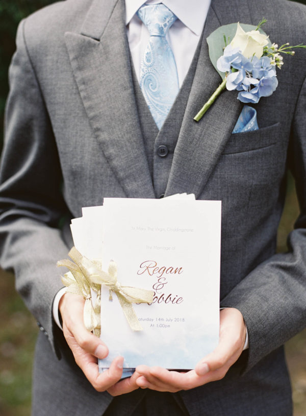 Groom holding gold, blue and white orders of service before church wedding ceremony