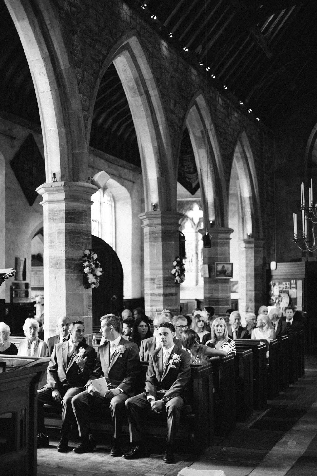 Black and white photograph of groom waiting for bride at the alter in Chiddingstone Church