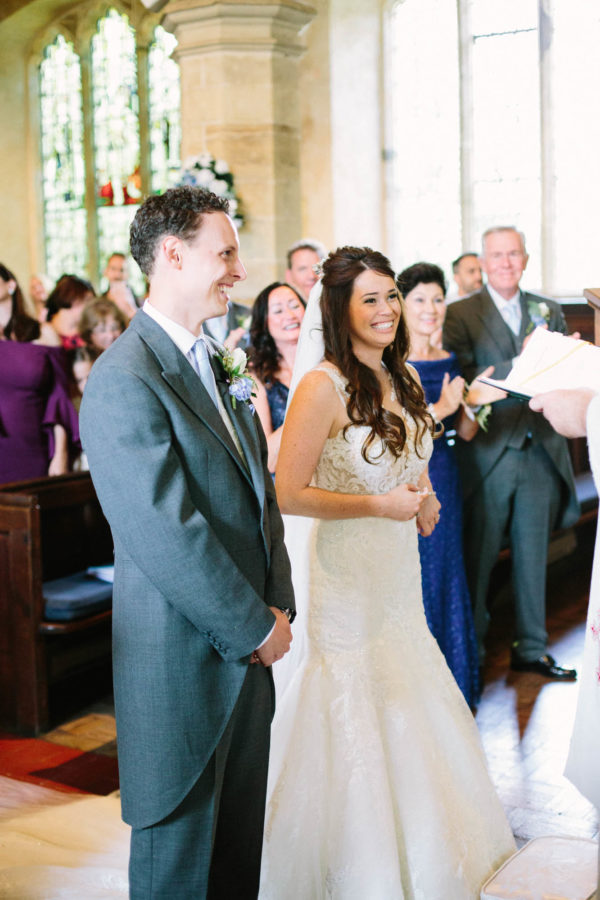 Bride and groom smiling and laughing during wedding service at Chiddingstone Church