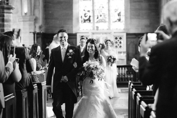 Bride and groom exiting church at Chiddingstone Castle wedding