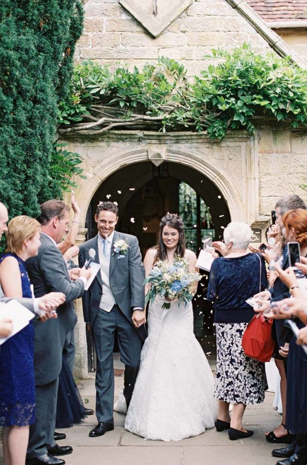 Bride and groom walking through confetti at Chiddingstone Church