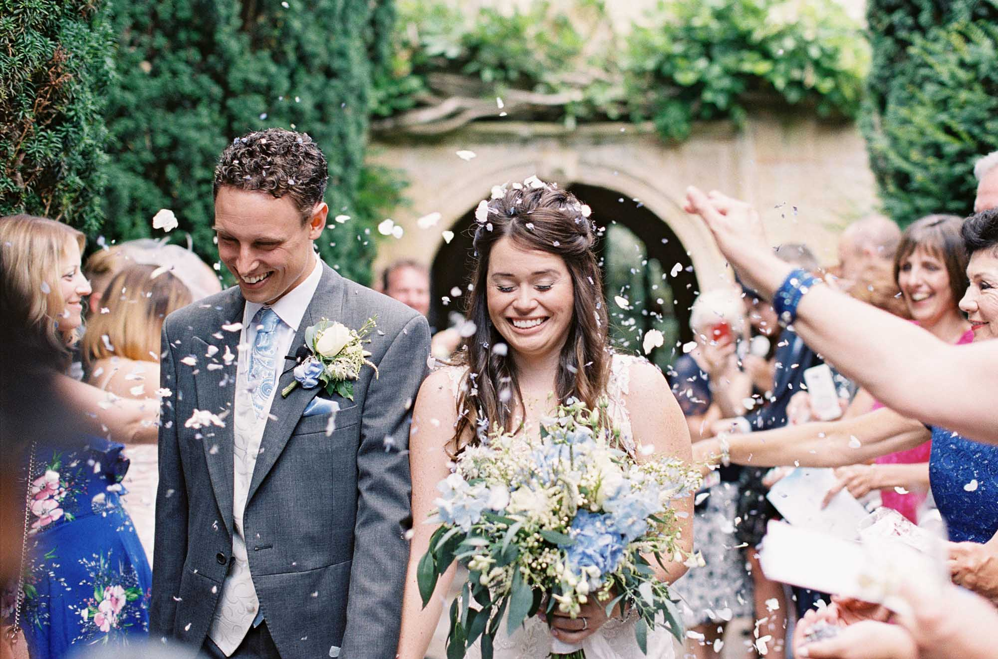 Bride and groom smiling during confetti throwing at Chiddingstone Church