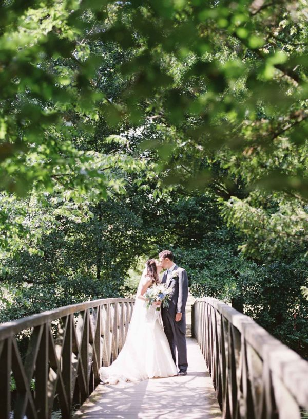 Romantic photograph of bride and groom on the bridge at Chiddingstone Castle wedding