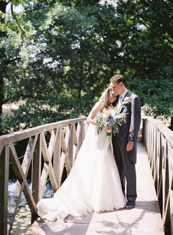 Elegant and timeless photograph of bride and groom hugging on the bridge at Chiddingstone Castle