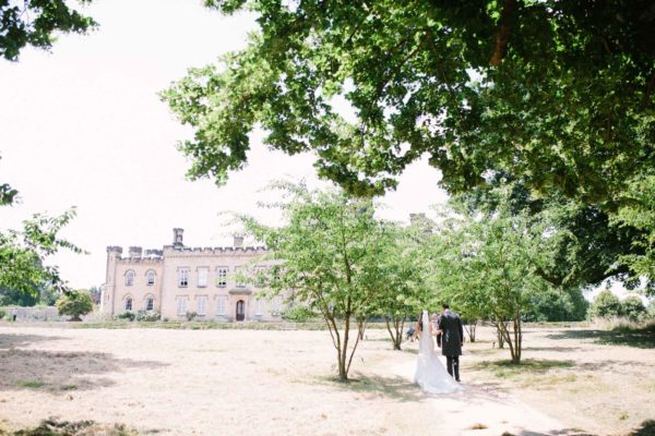 Bride and groom walking towards their Chiddingstone Castle wedding