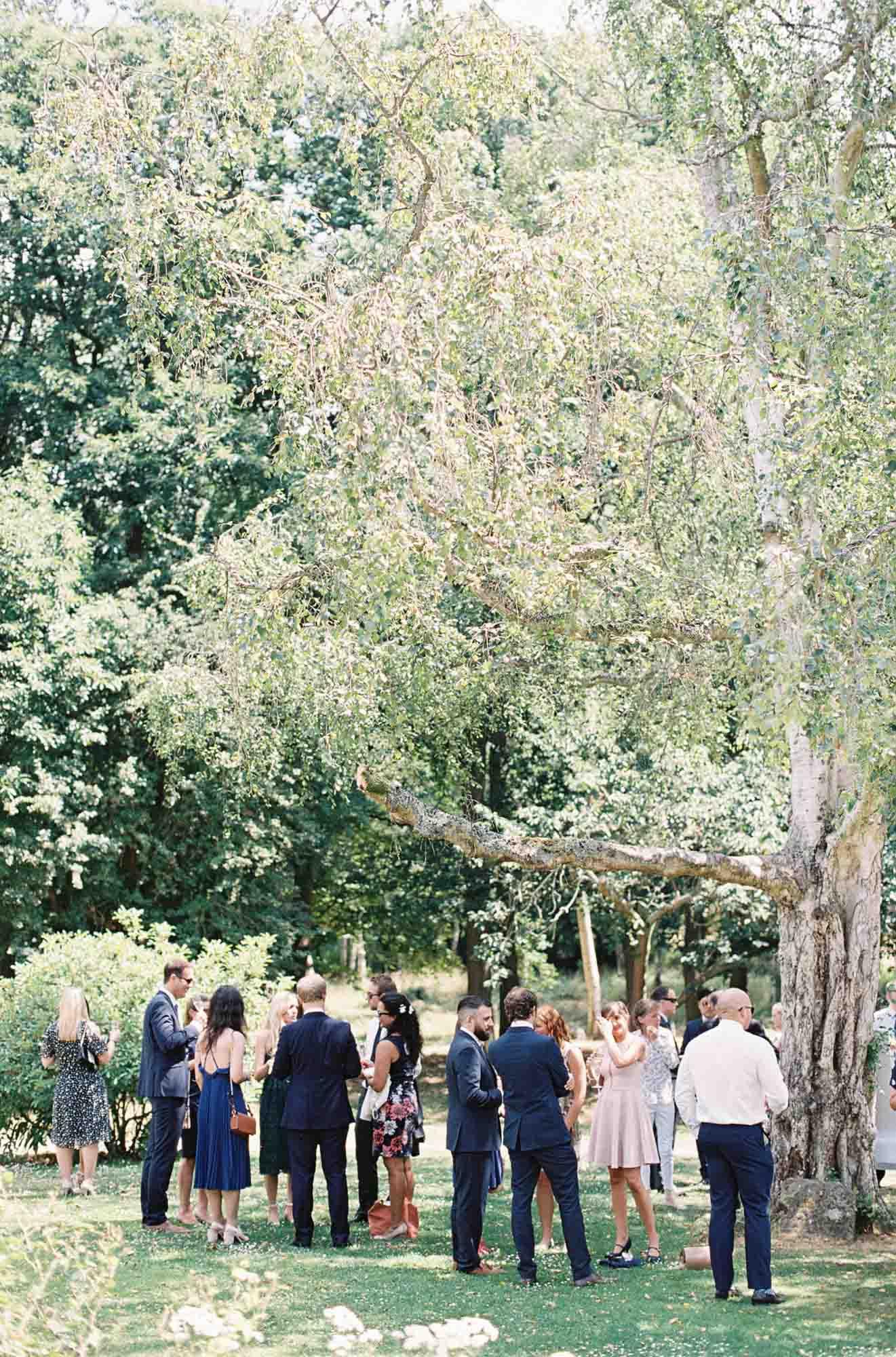 Guests mingling in the grounds of Chiddingstone Castle wedding