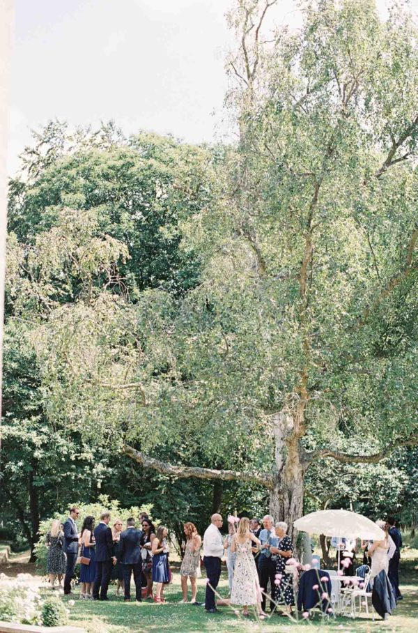 Guests on the lawn under a tree ar Chiddingstone Castle wedding