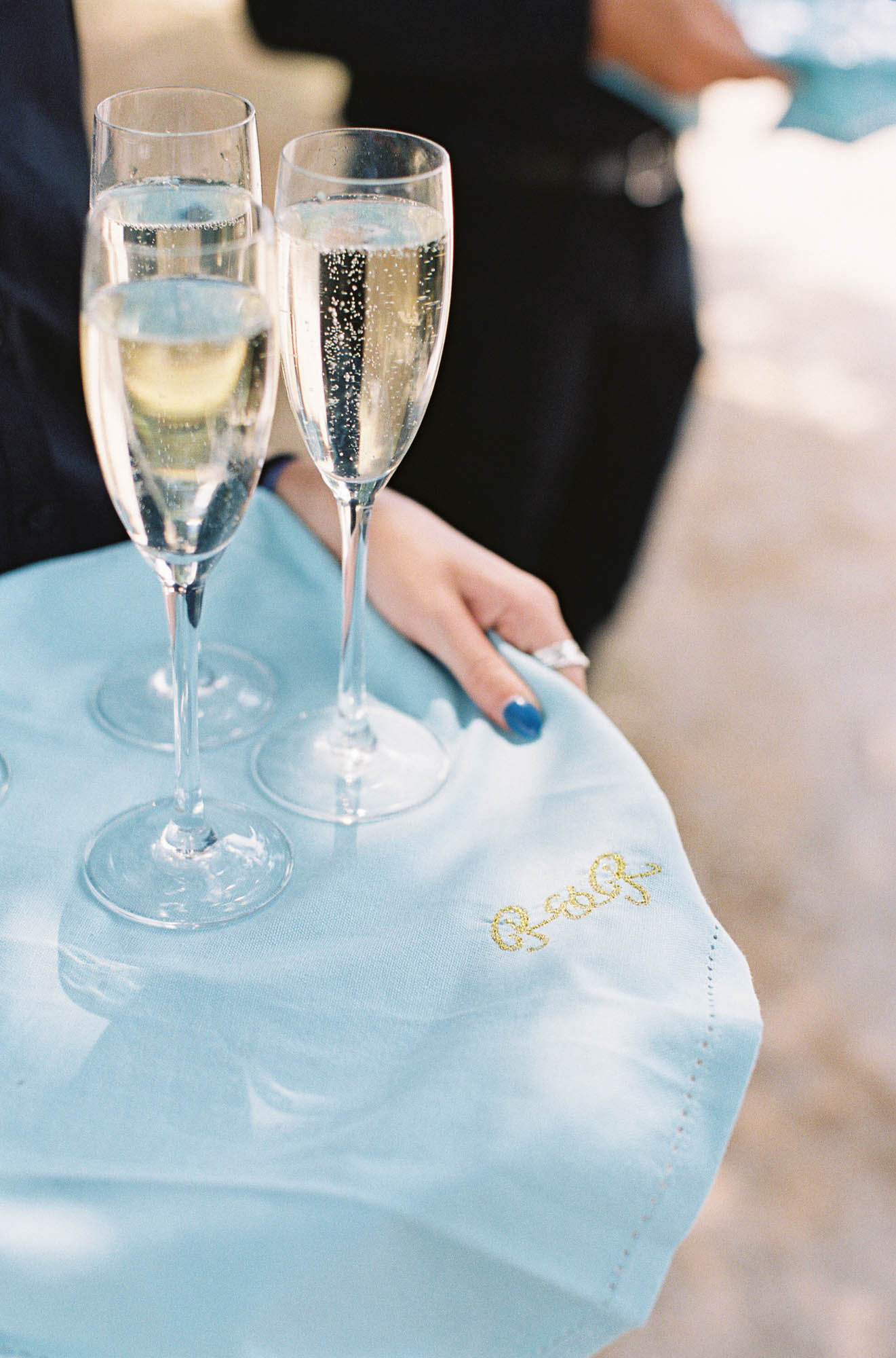 Champagne glasses on blue monogramed blue linen napkins