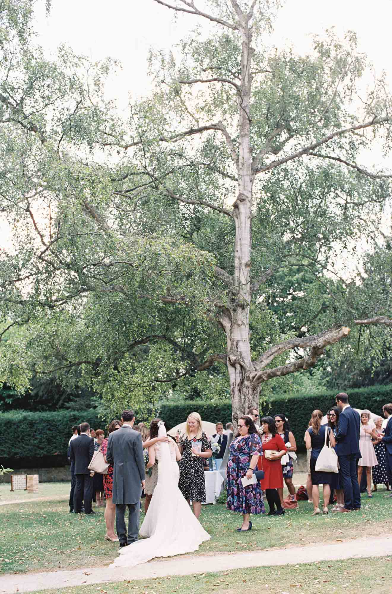 Guests hugging bride under large tree at Chiddingstone Castle wedding