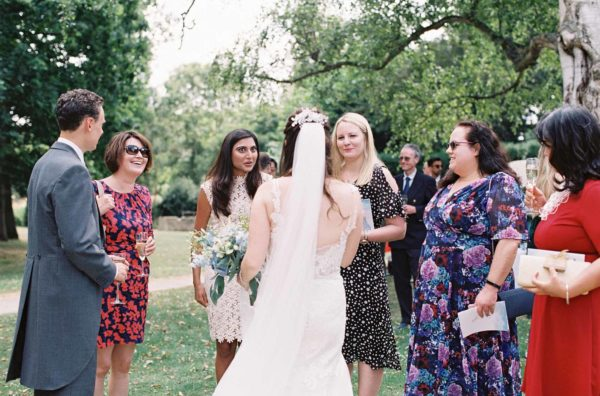 Bride chatting with guests at Chiddingstone Castle wedding