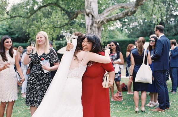 Guest hugging bride and smiling outside at Chiddingstone Castle wedding